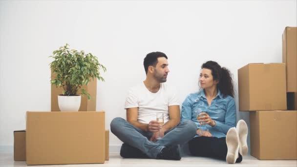 Šťastný pár sedí na podlaze a drží skleničky bílého vína. Akce. 4k.
