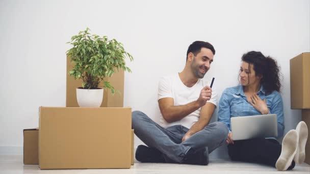 Das junge Paar zieht gemeinsam in eine neue Wohnung. Sie überlegen, wovon sie ausgehen sollen, wenn sie auf den Bildschirm des Laptops schauen. Aktion. Animation. 4k.