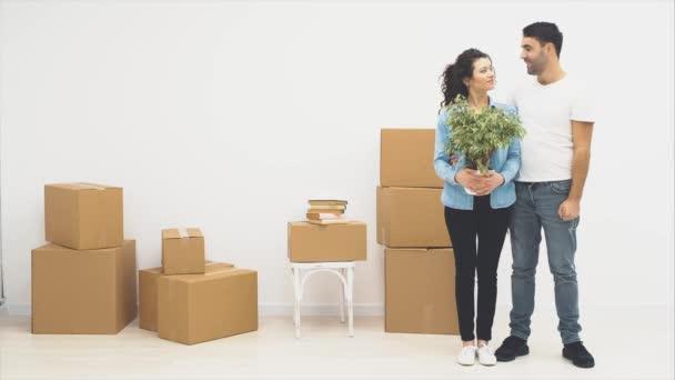 Das junge Paar zog gemeinsam in eine neue Wohnung. Frau hält einen Blumentopf, in dem die Wohnungsschlüssel versteckt sind. Sie kommen heraus. Kopierraum. Action, Animation. 4k.