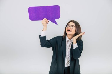 Portrait of an excited young business woman holding empty square violet speech bubble, looking at it, smiling.