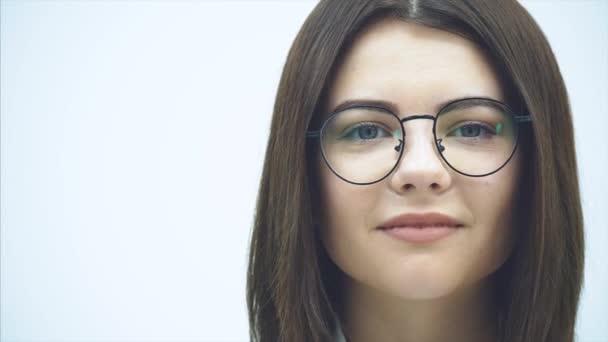 Zastřižená tvář atraktivní podnikatelky v brýlích, dívající se do kamery, usmívající se půvabně.