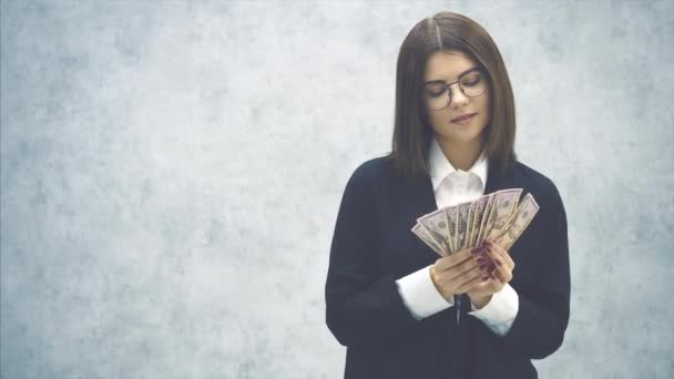 Confident young businesswoman, making a fan of money banknotes, smiling happily, dreaming.