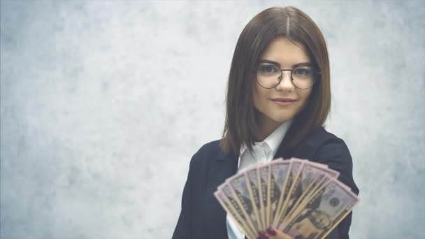 Confident young businesswoman extending a fan of dollar banknotes to the camera, posing, smiling enticingly and pleasantly. Blurred dollars on the forefront.