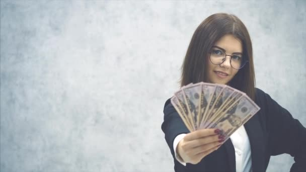 Confident young businesswoman extending a fan of dollar banknotes to the camera, posing, smiling, winking. Blurred dollars on the forefront.