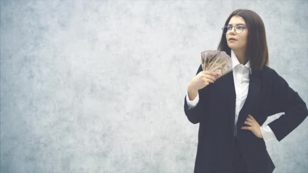 Cute young businesswoman in formal suit, her hand akimbo, waving a fan of money banknotes near her face, making wind. It is too hot.