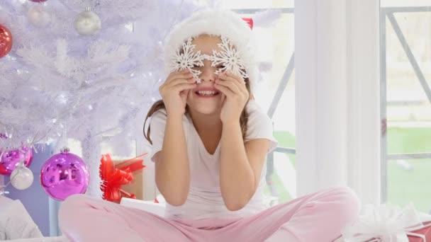 schöne Mädchen hält ihre Hände mit Dekor-Schneeflocken vor ihren Augen, lächelt schön und nimmt sie dann weg.