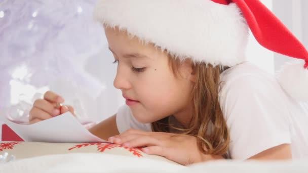 Inspirovaný kluk sedí pod vánočním stromečkem, píše vzkaz Nordovi, vypadá potěšeně a nadějně.
