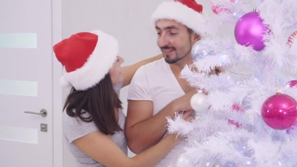Vnitřní video smyslného zamilovaného páru v chladné zimě Nový rok večer, zdobení stromu.