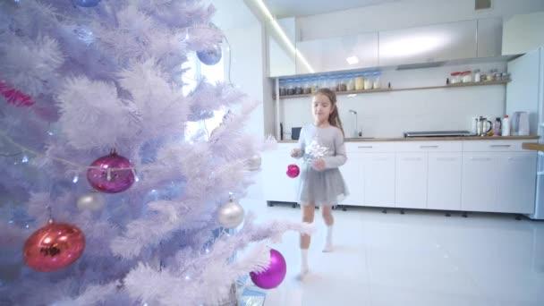 hübsches kleines Mädchen kommt an den Weihnachtsbaum auf der Vorderseite und legt eine Glaskugel auf einen der Zweige.