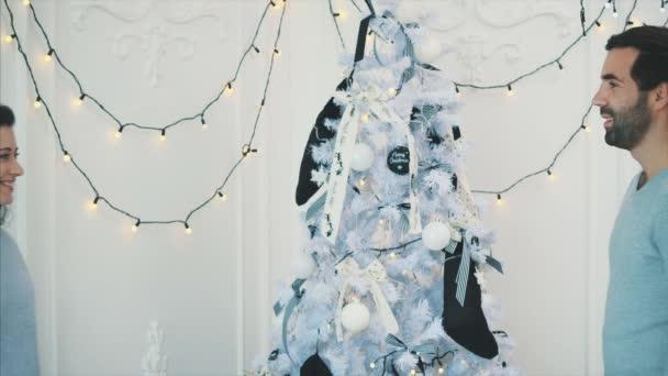 Milující pár setkat na Silvestra v blízkosti vánočního stromečku, líbání, dotýkání se čela a držet se za ruce.