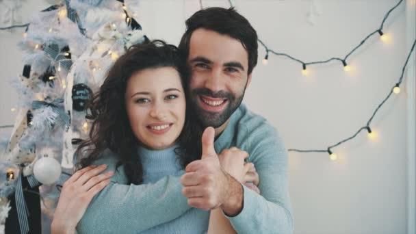 Neujahrs-Video von kindischem Paar, das Daumen nach oben gibt, umarmt und lächelt.