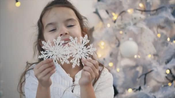 4k detailní video holčičky hrající si s vánoční strom sněhové vločky, skrývající své oči za nimi.