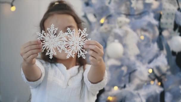 Malá dívka zdobí vánoční stromek se stříbrnými sněhovými vločkami doma a ukázat jim na kameru.