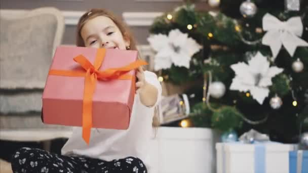 Closeup advertising video where little girl got a giftbox and presents it in front of the camera on Christmas background.