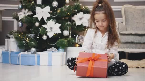 Licht 4k Video von niedlichen Kind sitzt mit Geschenk in den Händen, wie ein kleiner Gnom in Weihnachten dekorierten Raum.
