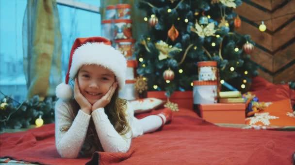 Weihnachtsmann-Kind legt sich auf die rote Decke unter dem Weihnachtsbaum, bewegt den Kopf von einer Seite zur anderen, hält die Hände auf die Wangen.