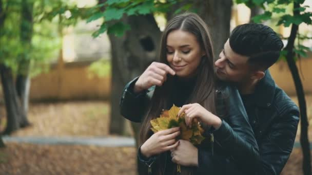 Boy in black leather coat is hugging his lovely girlfriend. He is holding a bunch of autumn leaves, and girl is picking up some and blows then in turn. Blurred background. Close up. Copy space. 4K.