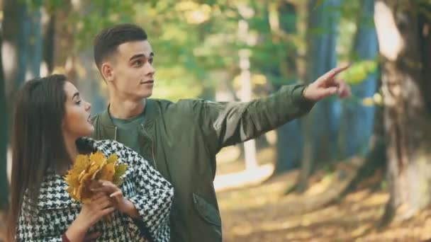Boy is hugging his lovely girlfriend. She is holding a bunch of autumn leaves, boy is pointing to something. Couple is waving on blurred background. Close up. Copy space. 4K.