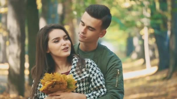 Boy is hugging his lovely girlfriend. She is holding a bunch of autumn leaves. Blurred background. Close up. Copy space. 4K.