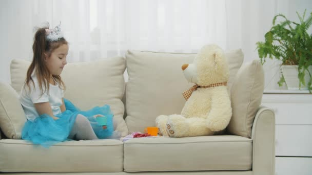 Baby girl playing in tea party, drinking from cup with best friend Teddy Bear sitting on the sofa. Blue dress and princess crown.