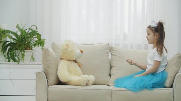 Kis tündér ül a kanapén varázspálcával a kezében, megidézi a játékmackóját, aztán a pálcát a kamerába irányítja..