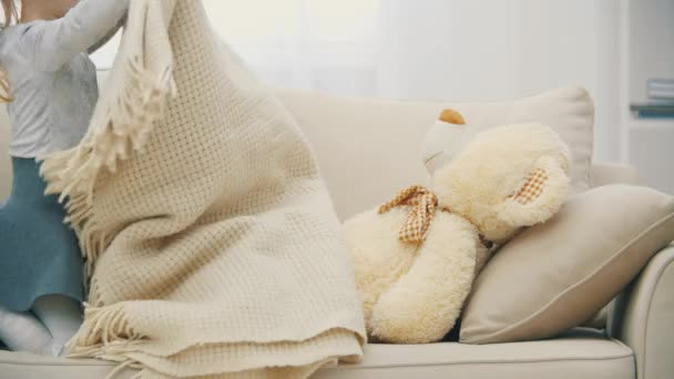 4k video of long-haired cute lying girl on sofa and covering a big teddy bear.