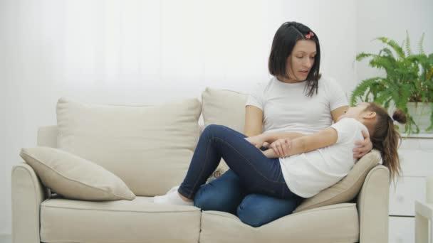4k zpomalení videa dcery a matky ležící na bílé pohovce v obývacím pokoji.