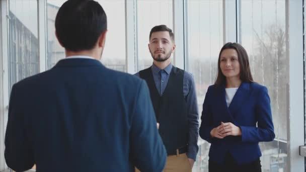 Šéf dává pokyny svým spolupracovníkům. Rozumím. Podřízení jsou šťastní. Rozmazané pozadí. Zavřít. Zadní pohled. 4K.