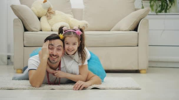 Hezká holčička s copánky se usmívá, objímá svého otce, který leží na podlaze, unavený a ospalý.