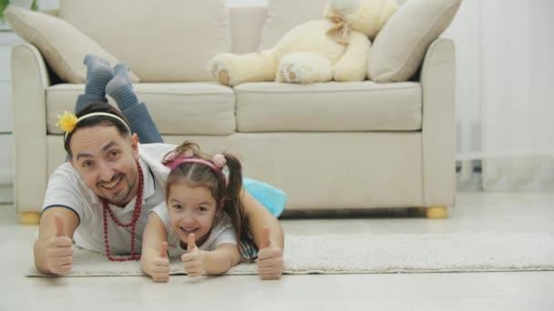 Živý otec a dcera v legračních pokrývkách hlavy si hrají, leží na podlaze, dávají palce nahoru, smějí se.