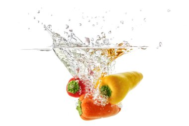Red and orange peppers fall into the water with splashes and bubbles,
