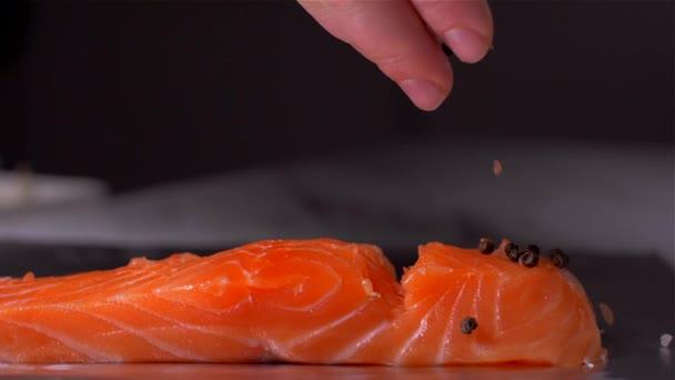 Só és bors hozzáadásával a lazac hal. Lassított mozgás