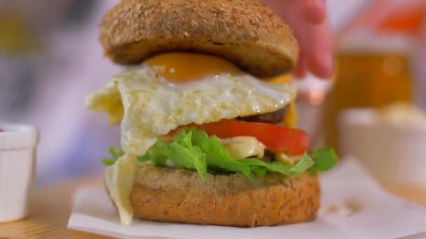 Cutting a juicy American burger. The yolk of the egg is flowing