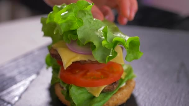 The chef builds a burger. A big plan. Slow motion