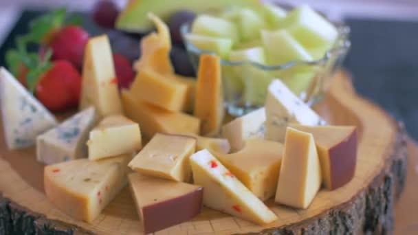 Různé druhy sýrů na dřevěné desce se otáčejí v kruhu