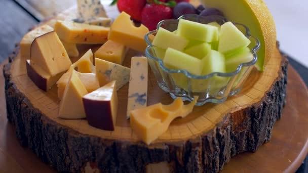 Krásné uspořádání různých druhů sýrů na dřevěné desce