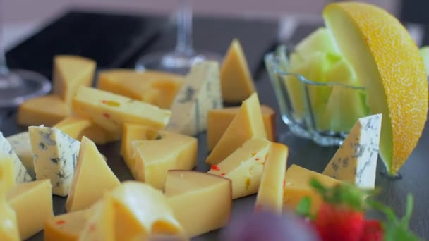 Různé druhy sýrů na černém kameni vypadají velmi chutně