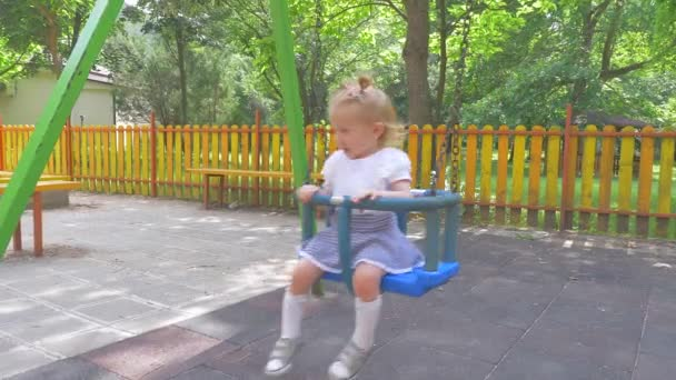 Cute smiling little baby girl swinging on a swing in summer day. Slow motion.