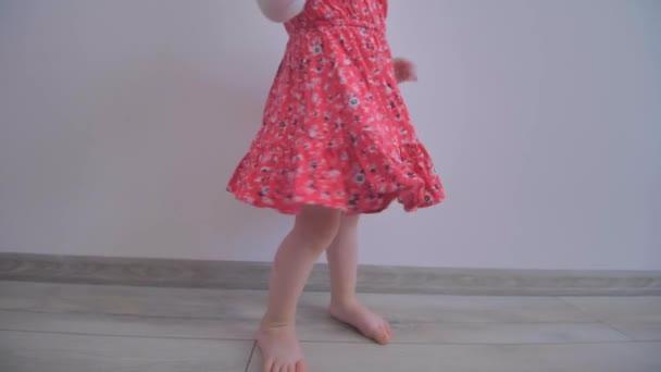 ein kleines blondes Mädchen mit rotem Kleid dreht sich und tanzt