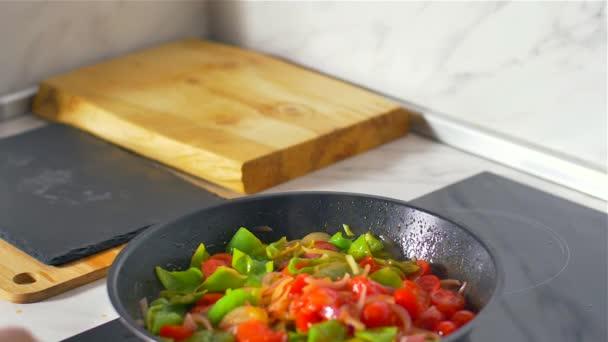 Der Koch rührt das Gemüse in der Pfanne um. Zeitlupe