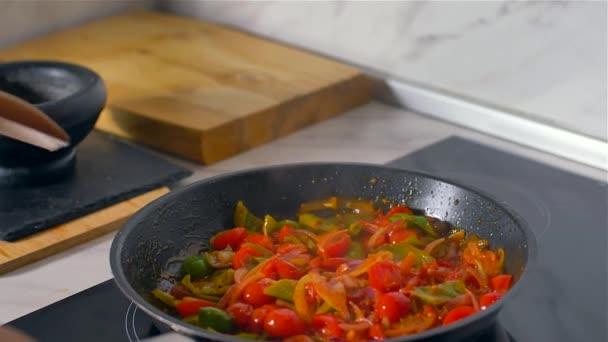 Der Koch rührt das Gemüse in der Pfanne mit einem Holzlöffel um. Zeitlupe