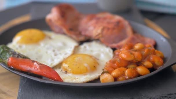 Snídaně, smažená vejce s klobásami, zelené fazole, rajčata. Podává se na dřevěném stole v restauraci. Closeup.