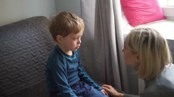 Ragazzino Upset che abbraccia la sua madre a casa