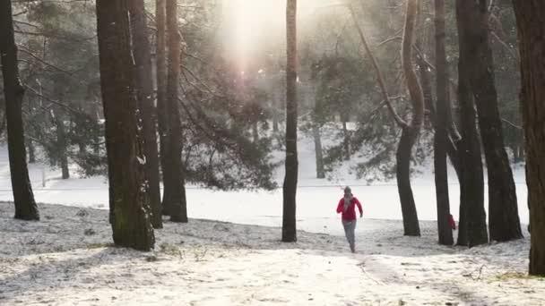 Weibliche Läufer Joggen im kalten Winterwald Warm sportlich laufen, Kleidung und Handschuhe tragen.