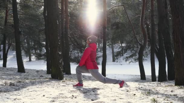 Woman warm up before jogging in cold winter forest wearing warm sporty running clothing and gloves. Beautiful fit female fitness model.