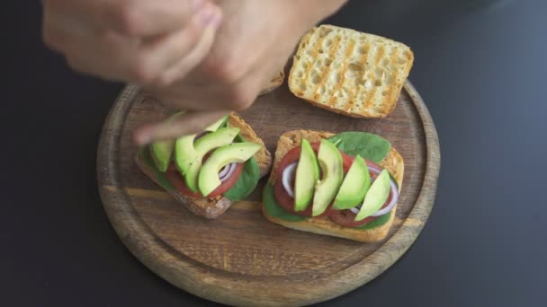 a man making sandwiches with avocado and tomatoes