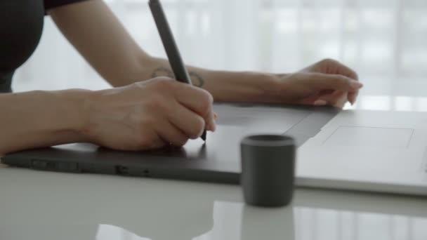 Női kéz használata digitalizáló tábla közelről. A laptop otthon dolgozó nő