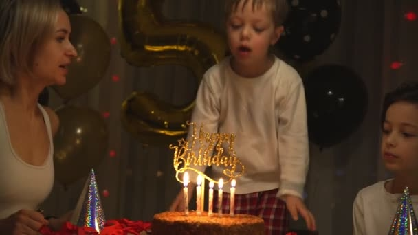 Junge pustet Kerzen auf Geburtstagstorte aus
