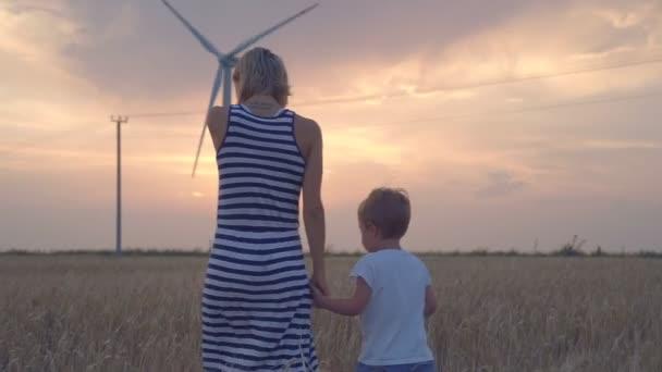 Mutter und Sohn spazieren mit Windrädern in Weizenfeld