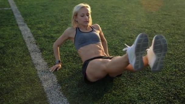 Fitness žena silový trénink dělá cvičení na fotbalové hřiště